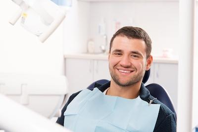 man smiling sitting in the dental chair