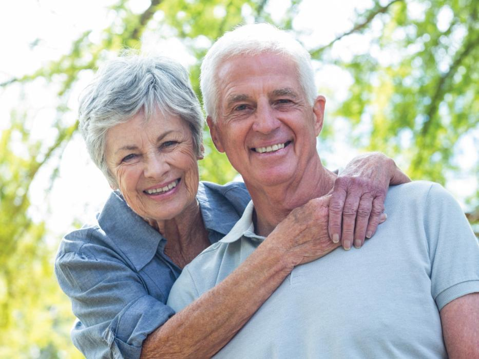 older couple smiling and holding one another outside