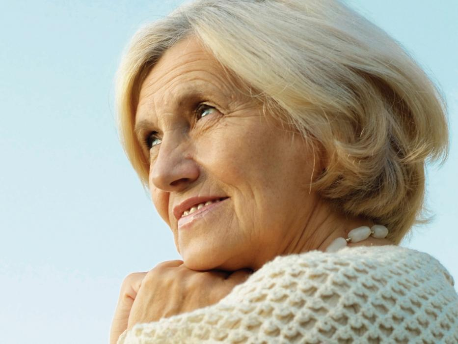 older woman subtly smiling while looking off into the distance