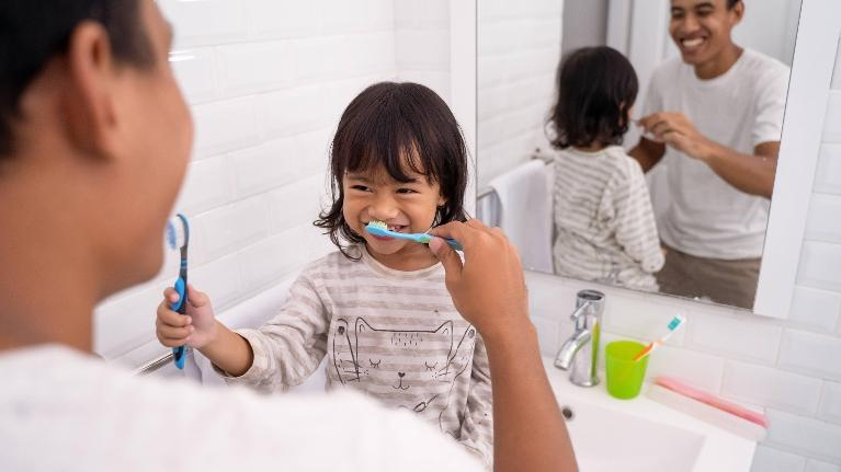 father and child brushing each others teeth